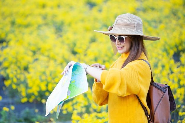 女性観光客は場所を見つけるために地図を持っています。 無料写真
