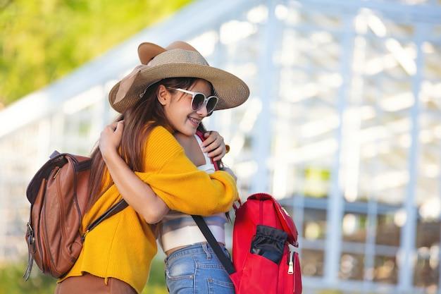 Female tourists walk holding arms Free Photo