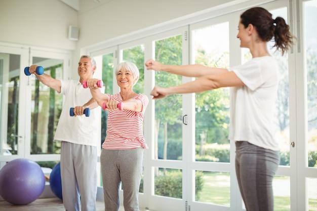 運動をすることで年配のカップルを支援する女性のトレーナー Premium写真