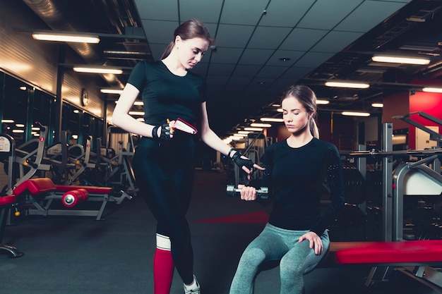 Female trainer assisting woman while exercising with dumbbell Free Photo