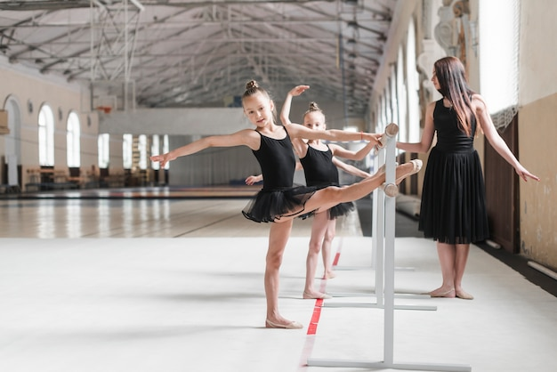 Female trainer looking at ballerina girls stretching their leg on barre Free Photo
