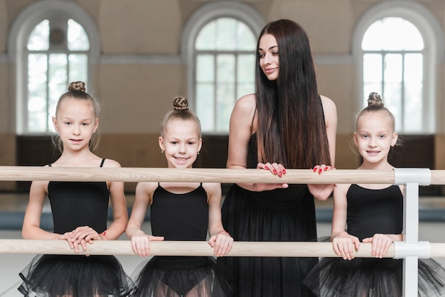 Female trainer looking at three ballerina girls standing behind the barre Free Photo