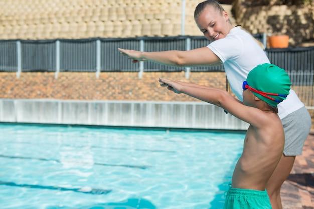 プールに飛び込むための男の子を訓練する女性のトレーナー Premium写真