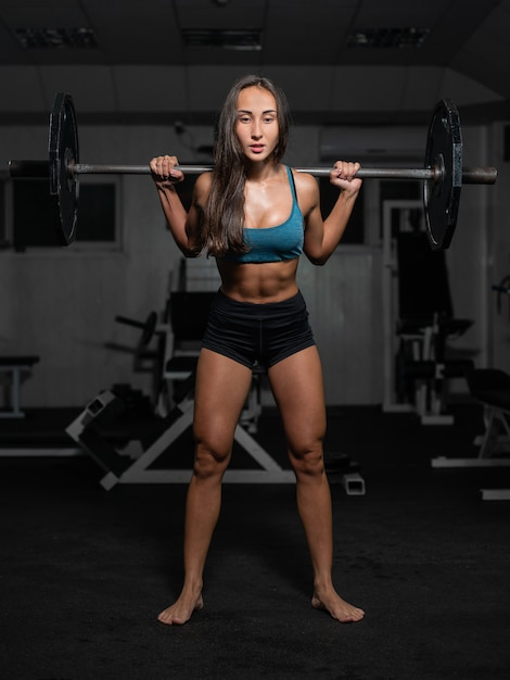 Female training with barbell, pumping legs Premium Photo