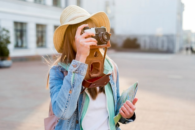 Female traveler holding map in hand taking picture with camera on city street Free Photo