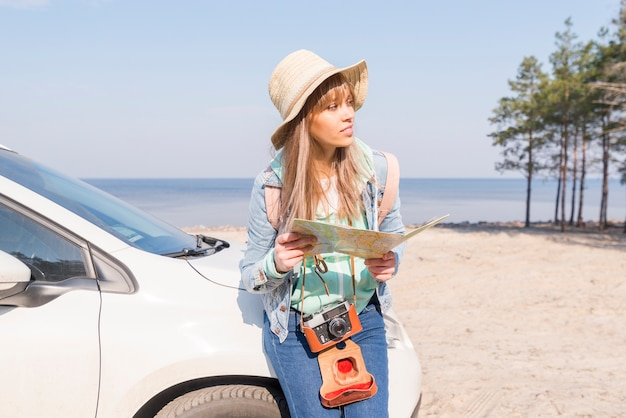 Female traveler leaning near the white car holding map in hand looking away Free Photo