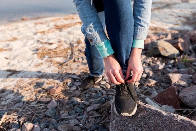 Female traveler tying the shoelace on beach Free Photo