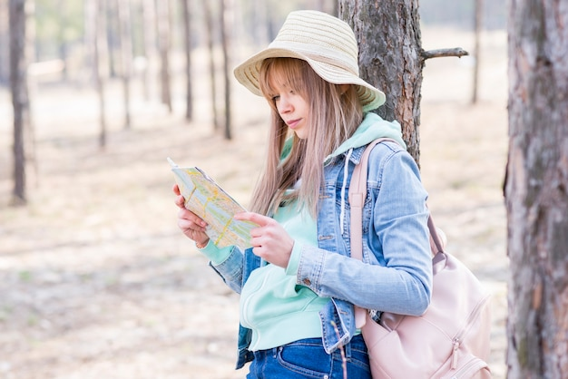 Female traveler with her backpack standing under the tree looking at the map Free Photo