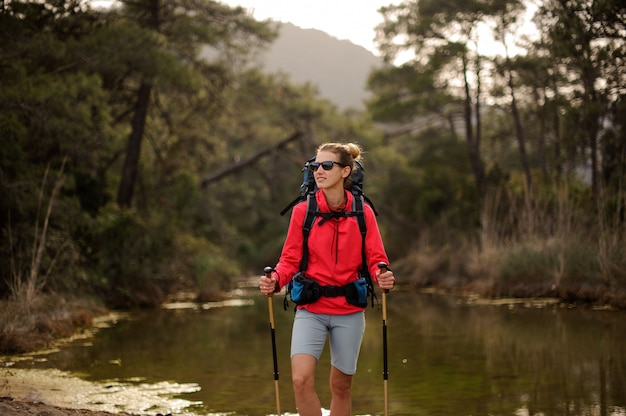 Female traveller stands by forest river shore Premium Photo