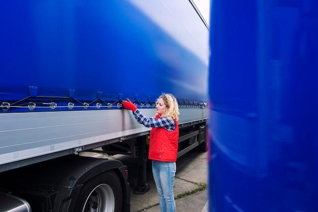 Водитель грузовика женского пола проверяет автомобиль и затягивает брезент грузовика Бесплатные Фотографии