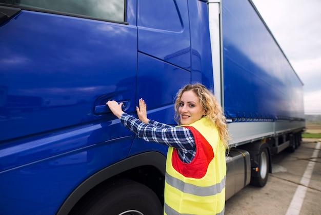 Autista di camion femminile che apre la porta della cabina e che entra nel veicolo del camion Foto Gratuite