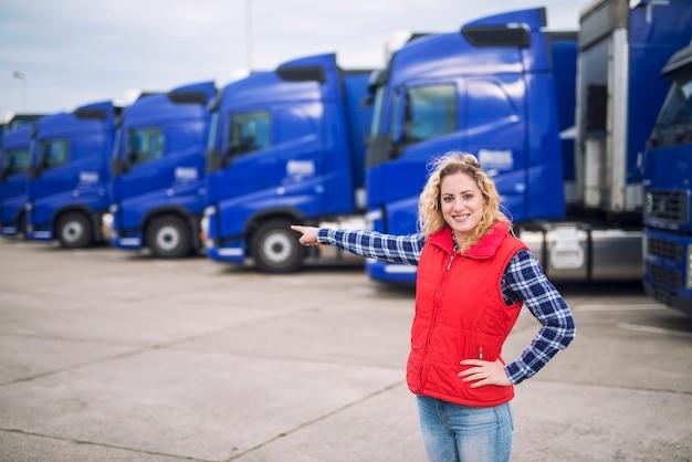 Camionista donna in piedi davanti a camion parcheggiati e puntando il dito verso i veicoli di trasporto Foto Gratuite