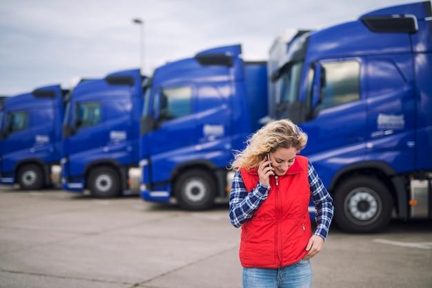 配達されなければならない積荷について電話で話している女性のトラック運転手 無料写真