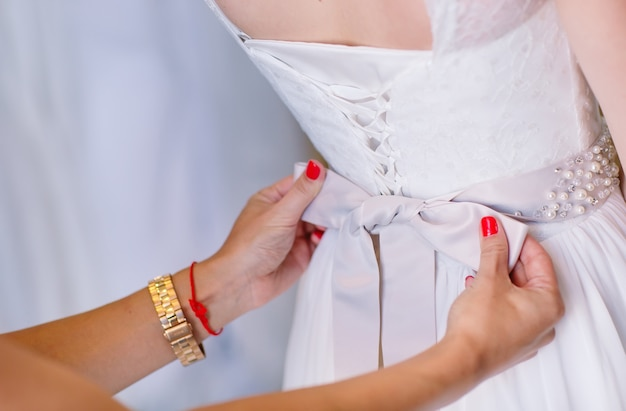 Female trying on wedding dress in a shop with women assistant. Premium Photo