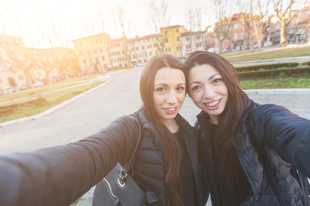 Female twins taking a selfie in the city. Premium Photo