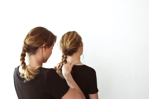 Female tying her sister's braid against white backdrop Free Photo