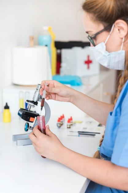 Female veterinarian examining blood sample in clinic Free Photo