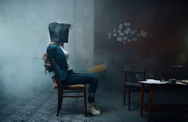 Женщина-жертва маньяка-похитителя с сумкой на голове. похищение - серьезное преступление, ужас похищения, насилие Premium Фотографии