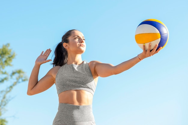 Female volleyball player serving ball in the beginning of game Free Photo