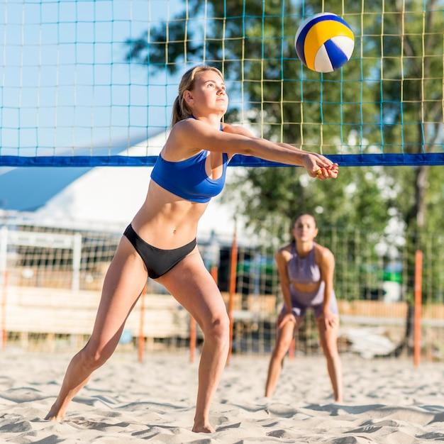 Giocatori di pallavolo femminile che giocano sulla spiaggia Foto Gratuite