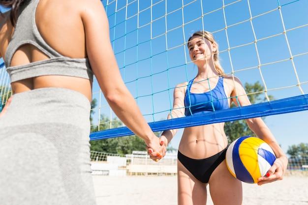 Giocatori di pallavolo femminili che agitano le mani sotto la rete Foto Gratuite
