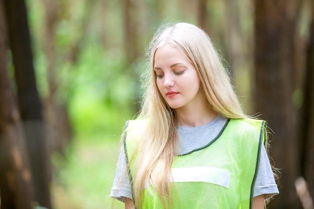 Женщина-волонтер держит пластиковый мешок для мусора, собирает мусор и кладет его в черный мешок для мусора. Premium Фотографии