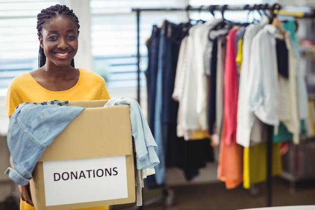 Female volunteer holding clothes in donation box Free Photo