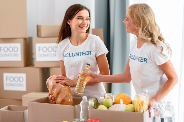 Женщины-волонтеры готовят продукты для пожертвований Premium Фотографии