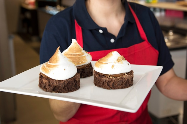 Female waitress holding chocolate cake with whipped cream in tray Free Photo