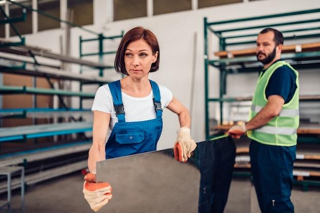 Female warehouse worker carrying stainless steel inox sheet metal Premium Photo