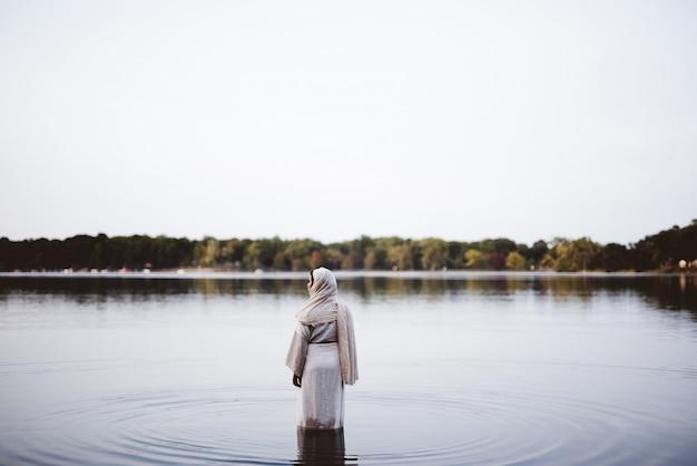水に立っている間聖書のローブを着ている女性-彼女の罪を清めるコンセプト 無料写真