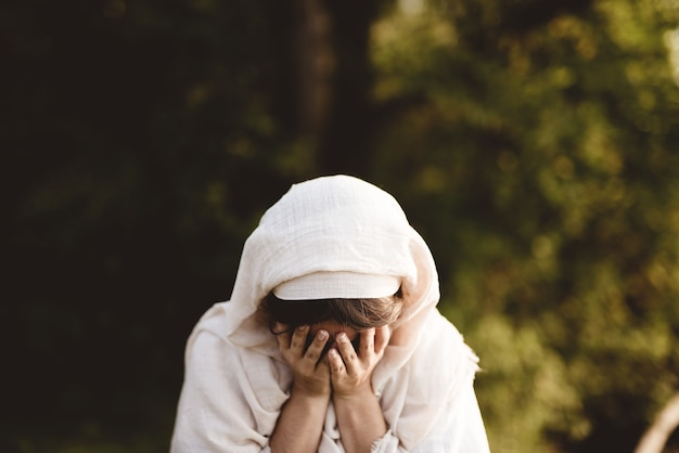 Female wearing biblical robe crying - concept confessing sins Free Photo
