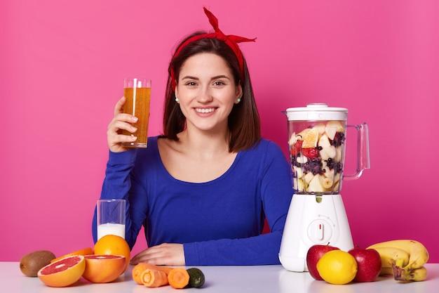 青いスウェットシャツと赤いヘッドバンドを身に着けている女性、彼女の健康のために栄養価の高い有用な混合物のガラスを保持 Premium写真
