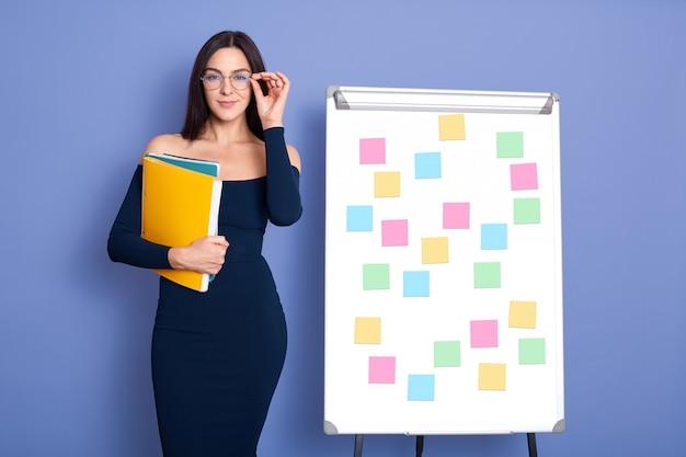 エレガントなドレスと立っている間手で紙のフォルダーを保持しているメガネを着ている女性は、青に分離されたステッカーとボードを聞く Premium写真