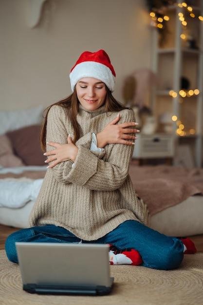 집에서 크리스마스 축하 기간 동안 노트북에 온라인 친구와 이야기하는 동안 웃는 산타를 입고 여성 무료 사진