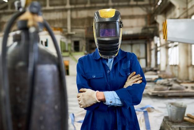 공장에서 포즈를 취하는 여성 용접기 프리미엄 사진