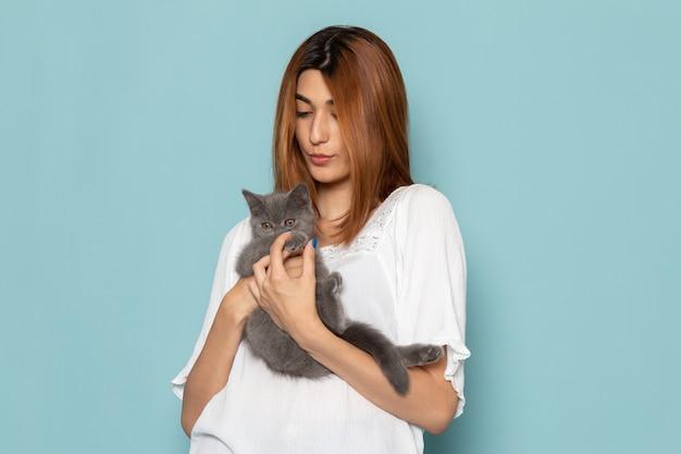 Femmina in abito bianco che tiene gattino carino grigio Foto Gratuite