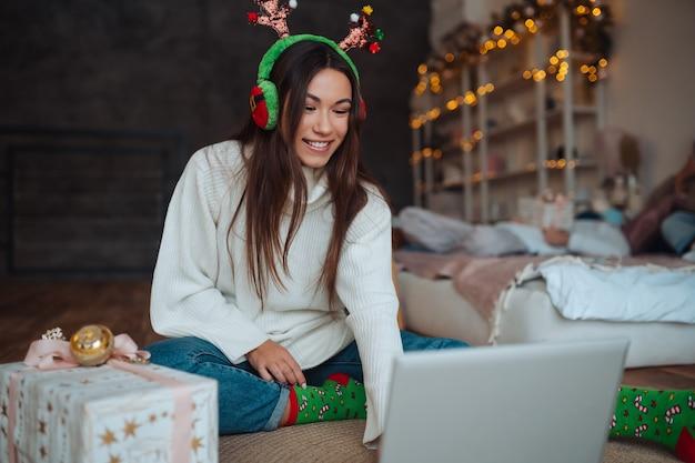 집에서 크리스마스 축하 기간 동안 노트북에 온라인 친구와 이야기하는 동안 웃고 뿔을 가진 여성 무료 사진