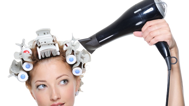 Female with black hairdryer drying female head in hair-curled - close-up Free Photo