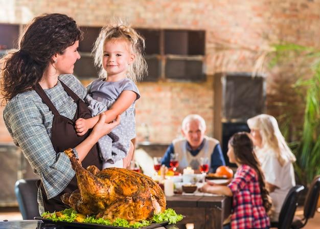 Female with child near roasted ham Free Photo