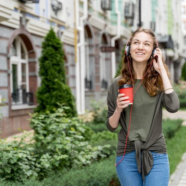 Женщина с кофе и наушниками Бесплатные Фотографии