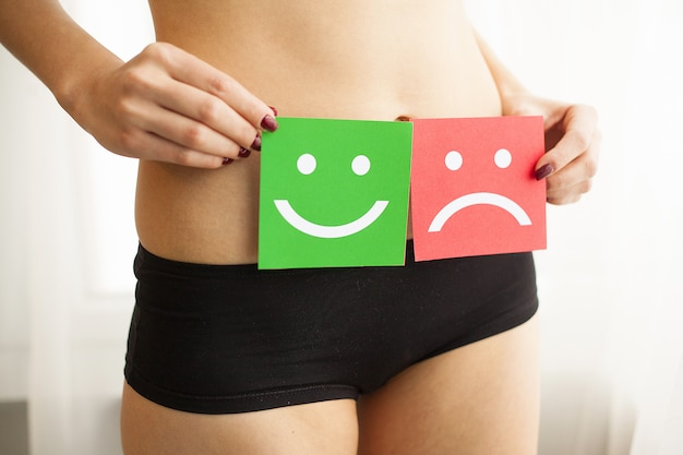 Female with fit slim body in panties holding two card with sad smiley and happy face near her stomach. Premium Photo
