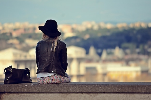 A female with a hat and a leather jacket sitting on the stone Free Photo