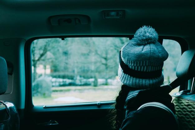 Femmina con un cappello seduto all'interno di un'auto guardando fuori dalla finestra Foto Gratuite