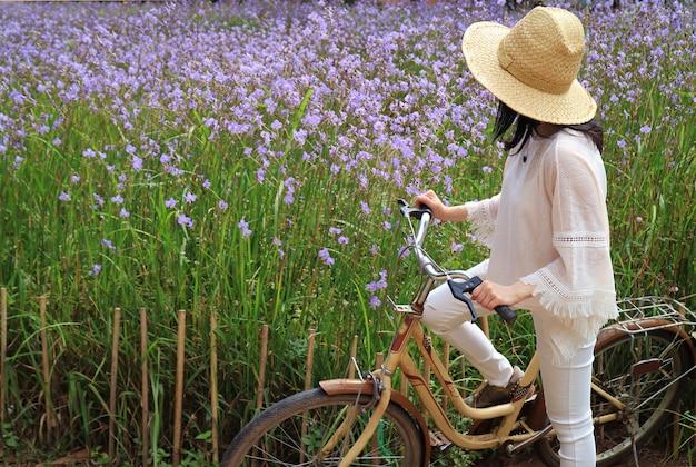 Female with her bicycle enjoy beautiful pastel purple flower field Premium Photo