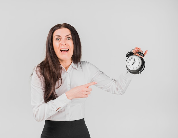Female with horrified face pointing out alarm clock Free Photo