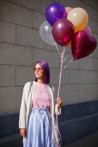 Female with purple hair in glasses with balloons looking to the right side Premium Photo