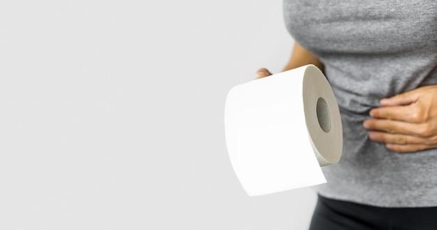 トイレットペーパーのロールを持つ女性 Premium写真
