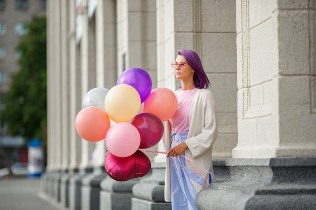 Female with violet hair in pink glasses standing with bunch of baloons Premium Photo