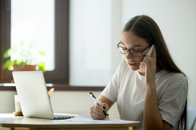 Female worker consulting client over phone Free Photo